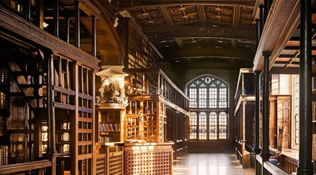 A large medieval era library with wooden shelves and a large glass window at one end of a corridor.
