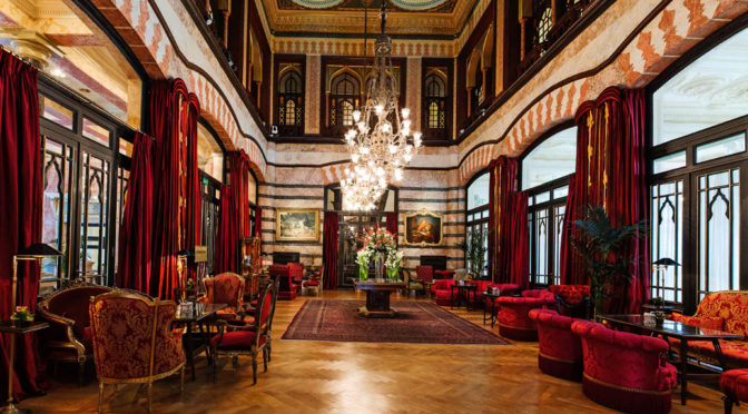 A plush hotel lobby with puffy red chairs lining beautiful windows. A chandelier dominates the center of the room.